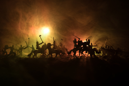 Medieval battle scene with cavalry and infantry. Silhouettes of figures as separate objects, fight between warriors on dark toned foggy background. Night scene. Selective focus Stock Photo - 97035512