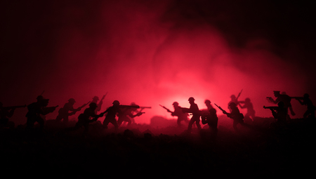 War Concept. Military silhouettes fighting scene on war fog sky background, World War Soldiers Silhouettes Below Cloudy Skyline At night. Attack scene. Armored vehicles. Tanks battle. Decoration Imagens