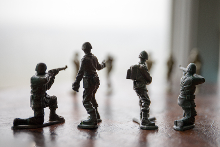 miniature toy soldiers and tank on board. Close up image of toy military at war. Selective focus