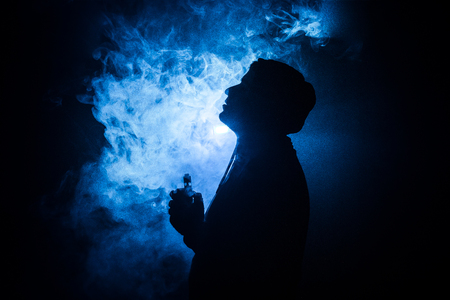 Vaping man holding a mod. A cloud of vapor. dark foggy toned background of clouds of smoke. Vaping an electronic cigarette with a lot of smoke. Vape concept. Selective focus