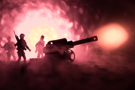 Battle scene with arillery and standing soldiers. Silhouette of old field gun standing at field ready to fire. With colorful dark foggy background. Selective focus