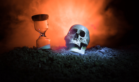 Skull and vintage hourglass on dark toned foggy background under beam of light. Horror concept. Empty space. Stock Photo