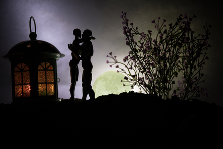 Silhouette of couple kissing under full moon. Guy kiss girl hand on full moon silhouette background. Valentine`s day decor concept. Big Lantern as lovers house