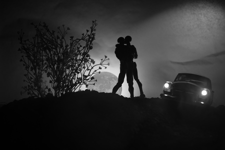 Silhouette of couple kissing under full moon. Guy kiss girl hand on full moon silhouette background. Valentine`s day decor concept. Car on back side