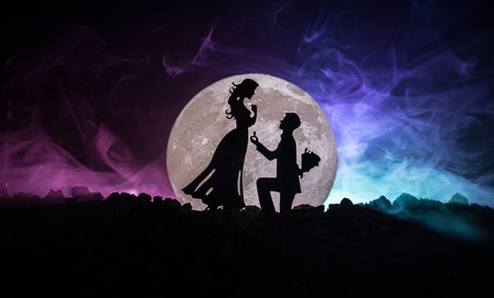Amazing love scene. Silhouettes of man making proposal to woman or Silhouettes of couple against big moon at background. Selective focus Archivio Fotografico