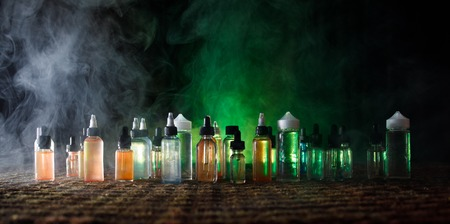 Vape concept. Smoke clouds and vape liquid bottles on dark background. Light effects. Useful as background or vape advertisement or vape background. Selective focus Stock Photo