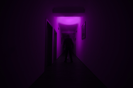 Dark corridor with cabinet doors and lights with silhouette of spooky horror man standing with different poses. Halloween concept