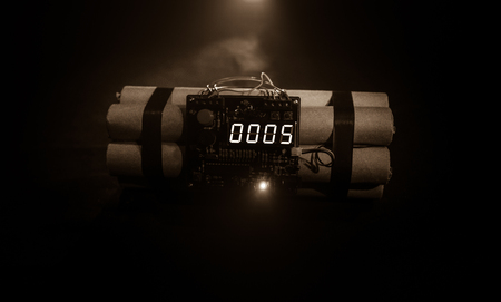 Image of a time bomb against dark background. Timer counting down to detonation illuminated in a shaft light shining through the darkness, conceptual image Reklamní fotografie