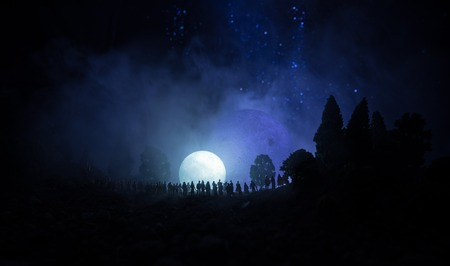 Silhouette of a large crowd of people in forest at night watching at rising big full Moon. Decorated background with night sky with stars, moon and space elements. Selective focus. Surreal world