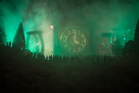 Silhouette of a large crowd of people in forest at night standing against a big arrow clock with toned light beams on foggy background. Time concept. Hourglass measuring the passing time