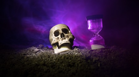 Skull and vintage hourglass on dark toned foggy background under beam of light. Horror concept. Empty space. Stock fotó
