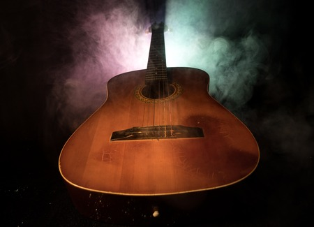 Music concept. Acoustic guitar on a dark background under beam of light with smoke. Guitar with Strings, close up. Selective focus. Fire effects.
