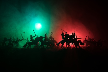 Medieval battle scene with cavalry and infantry. Silhouettes of figures as separate objects, fight between warriors on dark toned foggy background. Night scene. Selective focus 写真素材 - 101061396