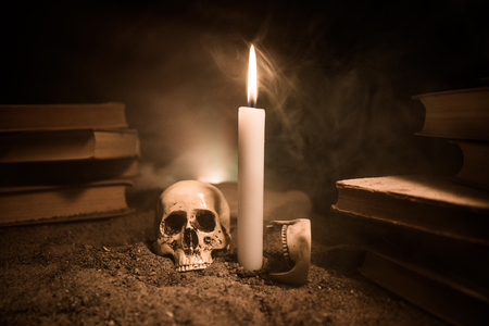 Wizards Desk. A desk lit by candle light. A human skull, old books on sand surface. Halloween still-life background with a different elements on dark toned foggy background. Selective focus