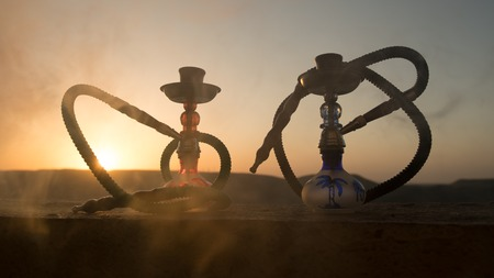Hookah, traditional arabic waterpipe, direct sunset light, outdoor photo. Mountain background or Silhouettes of hookah on sunset background. Outdoor. Selective focus Stock Photo