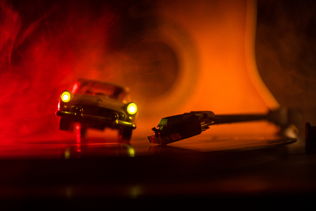Vintage vinyl record playing on player and acoustic guitar on background with fire orange smoke. Blues concept. With Toy car. Selective focus