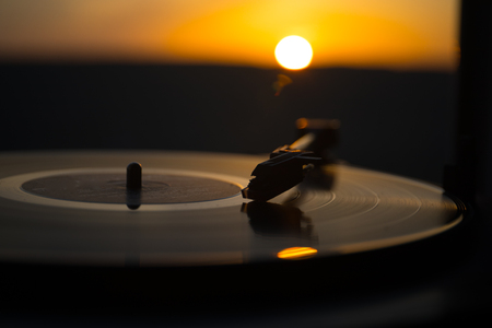 Turntable vinyl record player on the background of a sunset over the mountains. Sound technology for DJ to mix & play music. Black vinyl record. Vintage vinyl record player. Needle on a vinyl record