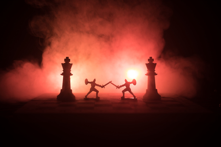 Medieval battle scene with cavalry and infantry on chessboard. Chess board game concept of business ideas and competition and strategy ideas Chess figures on a dark background with smoke and fog. Archivio Fotografico