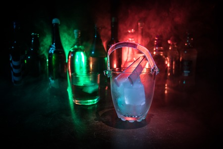 Glass ice bucket on blurred alcohol bottles background with lights and smoke. Club drinks concept. Club bar desk. Ready to serve. Selective focus