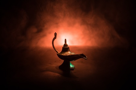 Antique Aladdin arabian nights genie style oil lamp with soft light white smoke, Dark background. Lamp of wishes concept. Selective focus Stockfoto