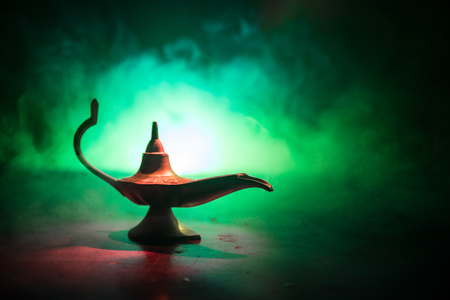 Antique Aladdin arabian nights genie style oil lamp with soft light white smoke, Dark background. Lamp of wishes concept. Selective focus 写真素材