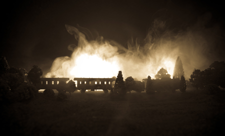 Train moving in fog. Ancient steam locomotive in night. Night train moving on railroad. toned foggy fire background. Horror mystical scene. Selective focus
