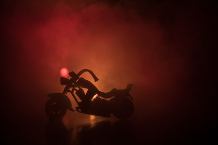 High power motorcycle chopper. Fog with backlights on background with man rider at night. Empty space. Selective focus Stock Photo
