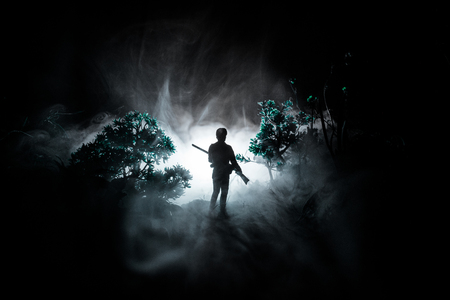 Man with riffle at spooky forest at night. Strange silhouette of hunter in a dark spooky forest at night, mystical landscape surreal lights with creepy man and wild bear. Selective focus