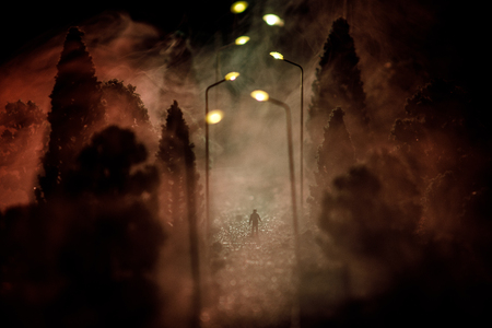 Lonely man. City at night in dense fog. Thick smog on a dark street. Silhouettes of man on road. Table decoration. Selective focus Stock Photo