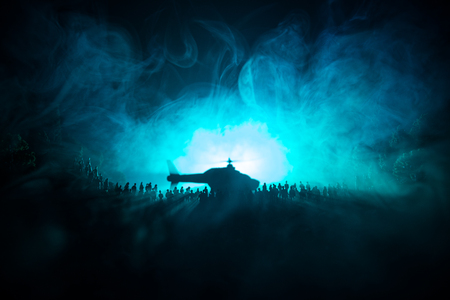 Military helicopter ready to fly from conflict zone or Silhouettes of a large crowd of people trying to escape with helicopter. Decorated night installed photo with foggy toned backlit