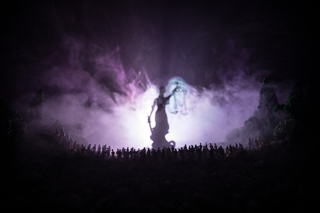 Justice and law concept. Silhouette of blurred giant lady justice statue with sword and scale standing behind crowd at night with foggy fire background. Selective focus