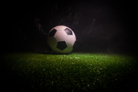 Traditional soccer ball on soccer field. Close up view of soccer ball (football) on green grass with dark toned foggy background. Selective focus Stock Photo