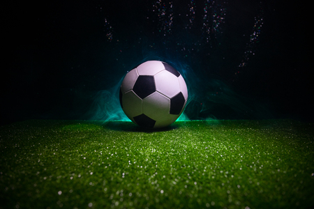 Traditional soccer ball on soccer field. Close up view of soccer ball (football) on green grass with dark toned foggy background. Selective focus Banco de Imagens
