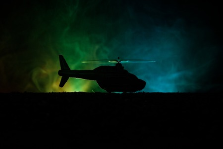 Silhouette of military helicopter ready to fly from conflict zone. Decorated night footage with helicopter starting in desert with foggy toned backlit. Selective focus. War concept Фото со стока