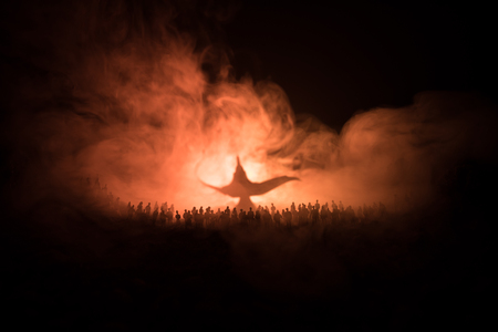 Lamp of wishes. Silhouette of a large crowd of people standing against a big lamp of wishes with toned light beams on foggy background. Dark night table decoration. Selective focus