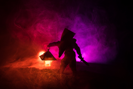 Man in raincoat coming from dark forest with glowing lantern in his hand concept. Silhouette of a horror killer with lamp. Decoration of Silent Hill monster Stock Photo