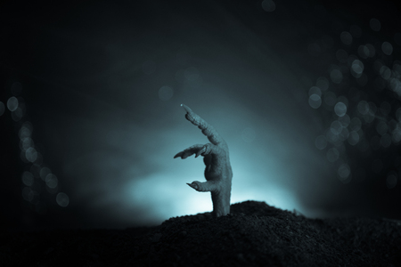 Halloween concept, zombie hand rising out from the ground or zombie hand coming out of his grave on dark toned foggy background