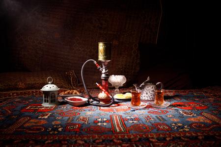 Hohe Wasserpfeifen der Shisha auf der Shisha-Schüssel, die Dampfwolken am arabischen Innenraum bilden. Orientalische Verzierung auf der östlichen Teezeremonie des Teppichs. Stilvolle orientalische Shisha im Dunkeln mit Hintergrundbeleuchtung. Selektiver Fokus Standard-Bild