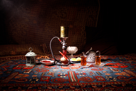 Hookah hot coals on shisha bowl making clouds of steam at Arabian interior. Oriental ornament on the carpet eastern tea ceremony. Stylish oriental shisha in dark with backlight. Selective focus Stockfoto