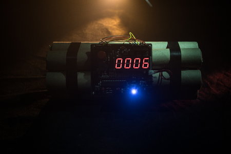 Image of a time bomb against dark background. Timer counting down to detonation illuminated in a shaft light shining through the darkness, conceptual image Stockfoto