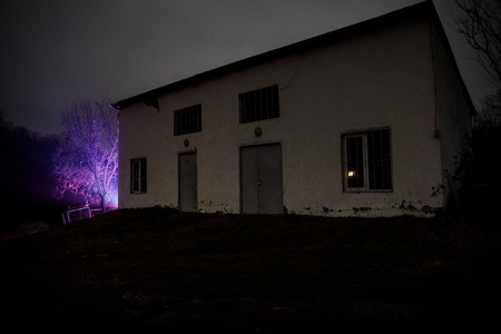 Old house with a Ghost in the forest at night or Abandoned Haunted Horror House in fog. Old mystic building in dead tree forest. Creepy house in the middle of a dark forest. Surreal lights Banco de Imagens