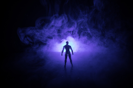 Silhouette of man standing on an dark foggy toned background. Decorated photo with man figure on table with light. Selective focus