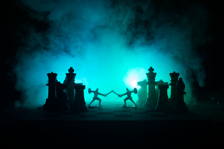 Medieval battle scene with cavalry and infantry on chessboard. Chess board game concept of business ideas and competition and strategy ideas Chess figures on a dark background with smoke and fog. 스톡 콘텐츠