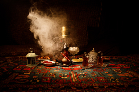 Hookah hot coals on shisha bowl making clouds of steam at Arabian interior. Oriental ornament on the carpet eastern tea ceremony. Stylish oriental shisha in dark with backlight. Selective focus Stock Photo