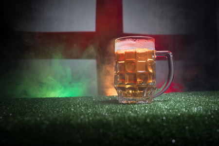Creative concept. Pint of fresh beer on grass with blurred flag of England on background or Glass of lager beer ready for drink. Copy space. Selective focus