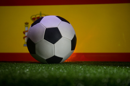 Traditional soccer ball on soccer field. Close up view of soccer ball (football) on green grass and Spain flag on background. Selective focus 스톡 콘텐츠