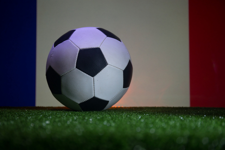Traditional soccer ball on soccer field. Close up view of soccer ball (football) on green grass and France flag on background. Selective focus