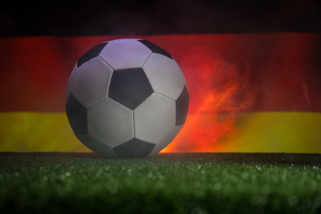 Traditional soccer ball on soccer field. Close up view of soccer ball (football) on green grass and German flag on background. Selective focus Stockfoto