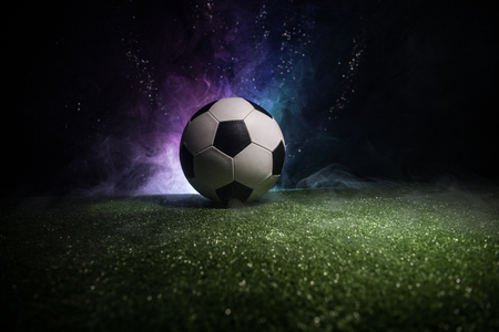 Traditional soccer ball on soccer field. Close up view of soccer ball (football) on green grass with dark toned foggy background. Selective focus Stockfoto