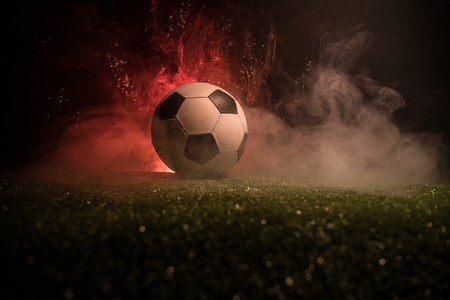 Traditional soccer ball on soccer field. Close up view of soccer ball (football) on green grass with dark toned foggy background. Selective focus 스톡 콘텐츠